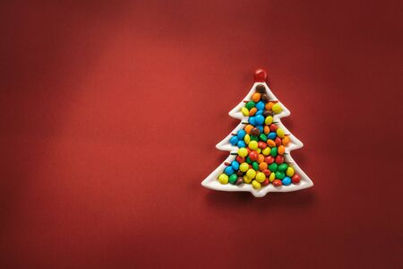 Christmas composition. A plate in the form of a Christmas tree filled with colorful candies on a red background. Flat lay, top view, copy space. Standard-Bild - 134039540