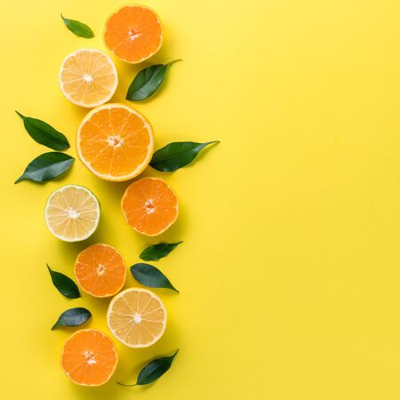 Creative background with tropical fruits. Orange, lemon, lime, grapefruit on a yellow background. Flat lay top view copy space. Nutrition Concept, Vitamin C, Disease Prevention, Flu 스톡 콘텐츠