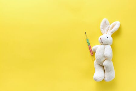 Childrens toy with a medical thermometer. Soft toy hare and medical thermometer on a yellow background. Chills in children. Temperature measurement in children. Flat lay. View from above. Copy space Standard-Bild - 134039533