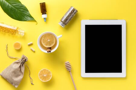 Illness concept. Composition alternative medicine. Herbal tea, ginger, lemon and gadget on a yellow background. Flat lay. View from above. Copy space Standard-Bild - 134039535