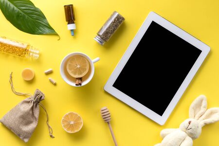 Illness concept. Composition alternative medicine. Herbal tea, ginger, lemon and gadget on a yellow background. Childs health. Flat lay. View from above. Copy space