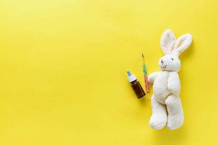 Childrens toy with a medical thermometer. Soft toy hare and medical thermometer on a yellow background. Chills in children. Temperature measurement in children. Flat lay. View from above. Copy space Standard-Bild - 134039538