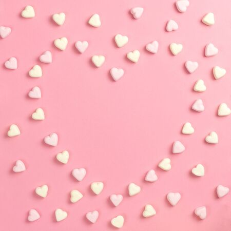 Composition for Valentines Day February 14th. Delicate pink background and yellow and pink marshmallows laid out in the shape of a heart. Greeting card. Flat lay, top view, copy space. Standard-Bild - 134039742