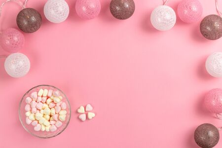 Composition for Valentines Day February 14th. Delicate pink background and garland. Heart shaped yellow and pink marshmallows. Greeting card. Flat lay, top view, copy space. Standard-Bild - 134039605
