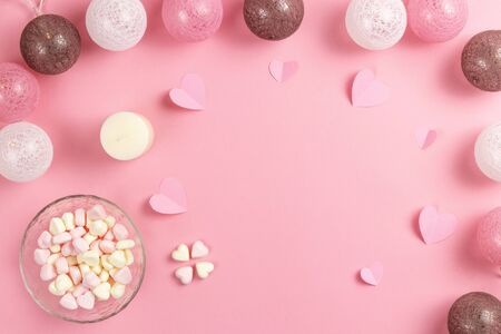 Composition for Valentines Day February 14th. Delicate pink background and a heart cut out of paper. pink heart-shaped marshmallows in a plate. Greeting card. Flat lay, top view, copy space. Standard-Bild - 134039749