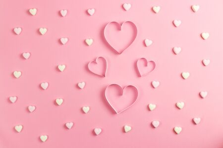 Composition for Valentines Day February 14th. Delicate pink background and a heart cut out of paper. Heart shaped yellow and pink marshmallows. Greeting card. Flat lay, top view, copy space Standard-Bild - 134039755