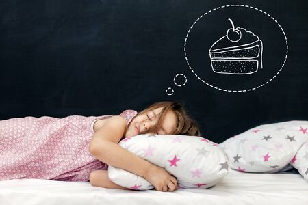 Charming little girl of preschool age sleeps in bed on a pillow with stars. Time to sleep. Happy childhood. Drawing about the dreams of a child: a piece of cake. Sweets. Copy space Standard-Bild - 134039767