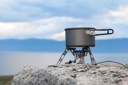 Tourist portable gas stove for preparing hot dishes and tea in the fresh air. A portable stove for outdoor activities, usually used for camping, hiking and other outdoor activities. Copy space Standard-Bild - 134278789