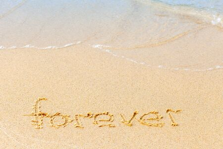 Text on a sunny beach. The word Forever written by hand in the sand, washed away by the sea wave. The concept of irony and transience of life. Copy space. Standard-Bild - 134278795