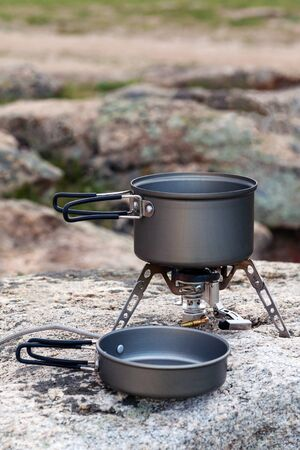 Tourist portable gas stove for preparing hot dishes and tea in the fresh air. A portable stove for outdoor activities, usually used for camping, hiking and other outdoor activities. Copy space Standard-Bild - 134278796