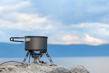 Tourist portable gas stove for preparing hot dishes and tea in the fresh air. A portable stove for outdoor activities, usually used for camping, hiking and other outdoor activities. Copy space Standard-Bild - 134278797