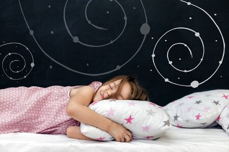 Charming little girl of preschool age sleeps in bed on a pillow with stars. Time to sleep. Abstract background about space and the dreams of a child. A journey in a dream. Happy childhood. Standard-Bild - 134278798