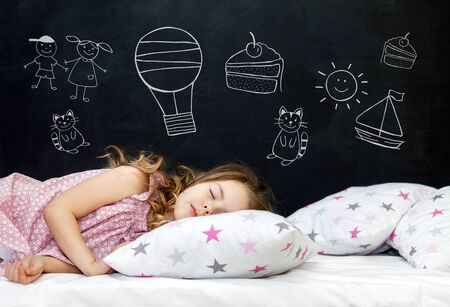 Charming little girl of preschool age sleeps in bed on a pillow with stars. Time to sleep. Drawing about the dreams of a child: kitten, dessert, adventure and friendship. Standard-Bild - 134278800
