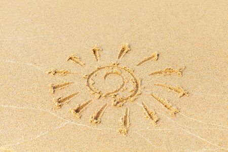 Drawing on a sunny beach. The sun is drawn by hand on the sand, washed away by the sea wave. Vacation concept on a sandy beach. Copy space. Standard-Bild - 134278804