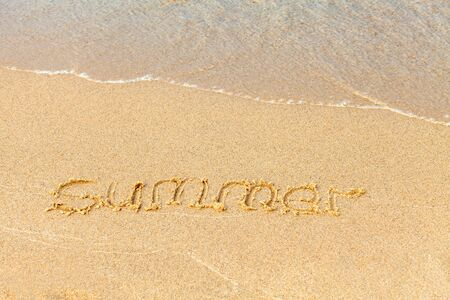Text on a sunny beach. The word Summer is handwritten in sand, washed away by a sea wave. Vacation concept on a sandy beach. Copy space. Standard-Bild - 134278805