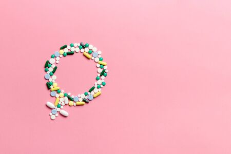 The concept of womens health and gynecology. Gender symbol made of pills on a pink background. Menopause, menstruation or estrogen concept.