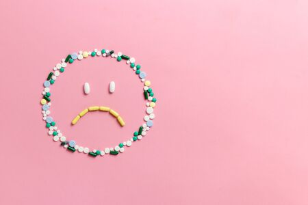 Composition of pills and capsules on a pink background in the form of emoji. Sad emotions. Psychological help. Copy space. View from above. Flat lay.
