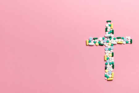The concept of deadly disease. Suicide. Death from improper treatment. Dangerous drugs. Composition of pills and capsules on a pink background in the form of a cross. Copy space. Flat lay. Banco de Imagens