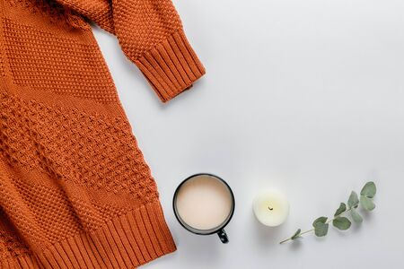 Winter composition. Orange sweater, candles and a eucalyptus branch on a white background. Autumn, winter concept. Flat lay, top view, copy space Banco de Imagens