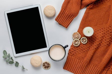 Autumn composition. Orange sweater and digital tablet with a cup of cocoa on a white table. Lifestyle, still life concept. Flat lay, top view.