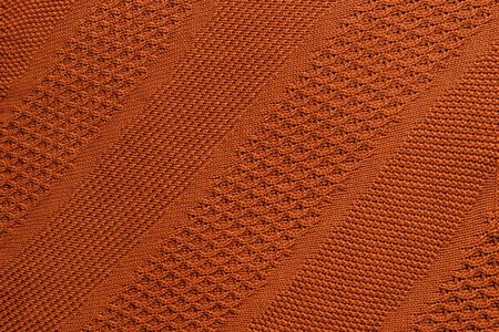 Orange knitted plaid closeup. Knitted texture with diagonal ornament. Detailed warm background made of yarn. Natural woolen fabric, fragment of a sweater for design. Copy space. View from above