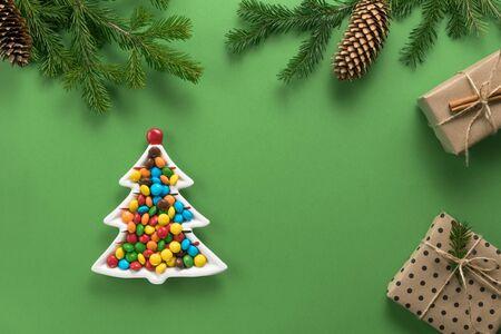 Christmas composition. Gifts and branches of spruce. A plate in the form of a Christmas tree filled with colorful candies on a green background. Flat lay, top view, copy space