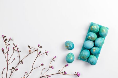Happy easter card. Stylish minimalistic composition of turquoise with gold easter eggs on a white background. Delicate spring flowers. Flat lay, top view, copy space.