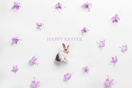 Happy easter card. Stylish minimalistic composition on a white background. Figurine of a rabbit and delicate spring flowers. Flat lay, top view, copy space.