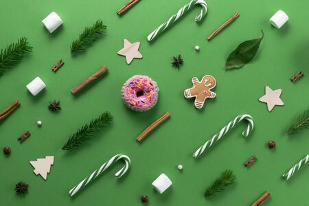 Christmas composition. Creative christmas background. Christmas decorations and fir branches create an ornament and texture on a green background. Flat lay, top view, copy space. Banco de Imagens