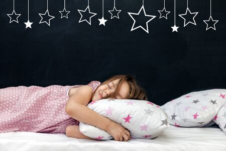 Charming little girl of preschool age sleeps in bed on a pillow with stars. Time to sleep. Abstract background about space and the dreams of a child. A journey in a dream. Happy childhood Standard-Bild - 135223120