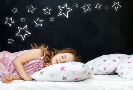 Charming little girl of preschool age sleeps in bed on a pillow with stars. Time to sleep. Abstract background about space and the dreams of a child. A journey in a dream. Happy childhood