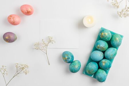Happy easter card. Stylish minimalistic composition of turquoise with gold easter eggs on a white background. Candles and delicate spring flowers. Flat lay, top view, copy space. Standard-Bild - 135265518