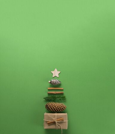 Christmas composition. Creative christmas background. Christmas decorations and gifts in the form of a Christmas tree against a green background. Flat lay, top view, copy space. Standard-Bild - 135266374