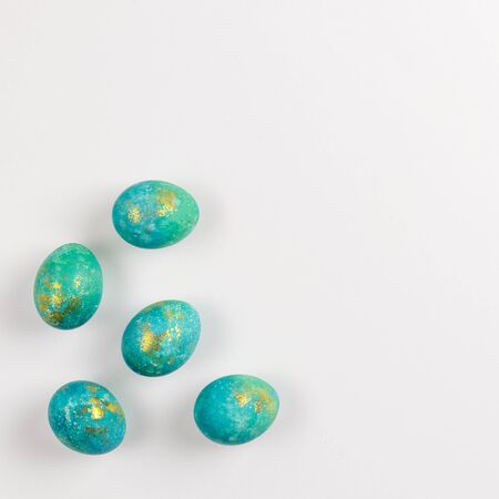 Happy easter card. Stylish minimalistic composition of turquoise with gold easter eggs on a white background. Flat lay, top view, copy space Standard-Bild - 135269532