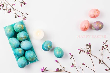 Happy easter card. Stylish minimalistic composition of turquoise with gold easter eggs on a white background. Candles and delicate spring flowers. Flat lay, top view, copy space Standard-Bild - 135417962