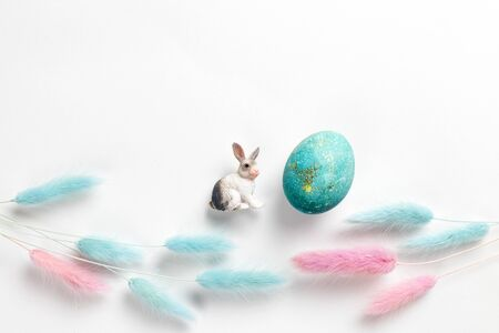 Happy easter card. Stylish minimalistic composition of turquoise with gold easter eggs on a white background. Figurine of a rabbit and delicate spring flowers. Flat lay, top view, copy space Standard-Bild - 135418041
