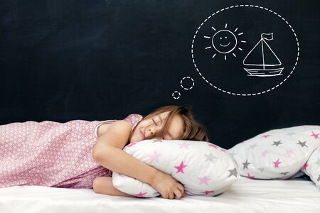 Charming little girl of preschool age sleeps in bed on a pillow with stars. Time to sleep. Drawing about the dreams of a child. Copy space Standard-Bild - 135423927