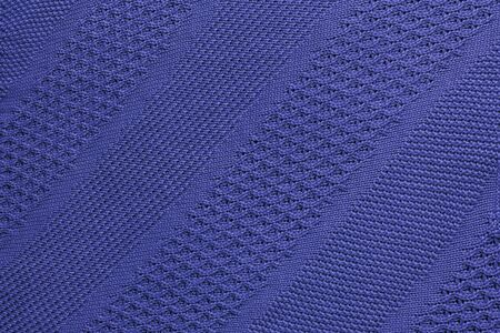 Dark blue knitted plaid closeup. Knitted texture with diagonal ornament. Detailed warm background made of yarn. Natural woolen fabric, fragment of a sweater for design. Copy space Top view.