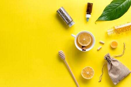 Illness concept. Composition alternative medicine. Herbal tea, ginger and lemon on a yellow background. Childs health. Flat lay. View from above. Copy space