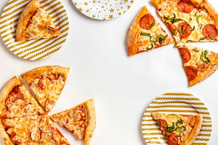 Slices of delicious fresh pizza with pepperoni and cheese on a white plate. Birthday with junk food. Top view with copy space for text. Flat lay