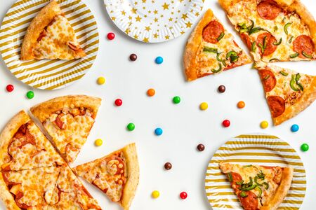 Pieces of pizza and colored sweets on a white background. Birthday with junk food. Children's party. Top view with copy space for text. Flat lay.
