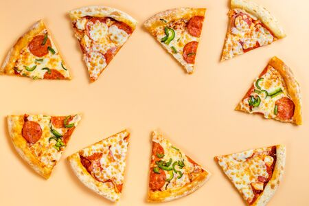 Sliced pizza in the form of a frame for a party. Pieces of pizza on a beige background. Space for text. Pizza menu. Birthday with junk food
