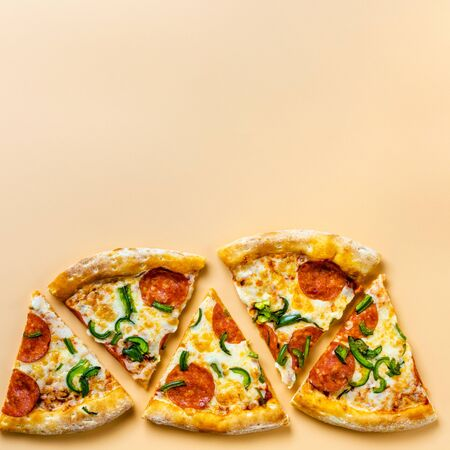 Pieces of pizza on a beige background. Space for text. Pizza menu. Birthday with junk food