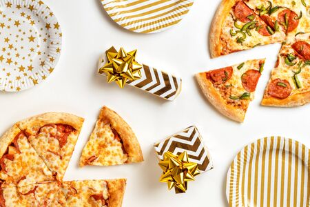 Birthday with junk food. Two large tasty pizzas with pepperoni and cheese on a white plate. Gifts on the holiday table. Top view with copy space for text. Flat lay. Banco de Imagens