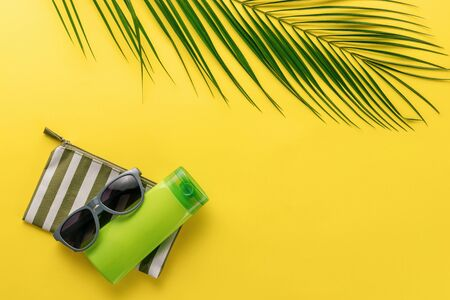 Summer background. Composition striped beach cosmetic bag with sunblock and sunglasses on a yellow background. Summer vacation concept, sunscreen cosmetics and accessories. Top view. Copy space.