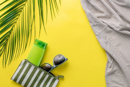 Summer background. Composition striped beach cosmetic bag with sunblock and sunglasses on a yellow background. Summer vacation concept, sunscreen cosmetics and accessories. Top view. Copy space