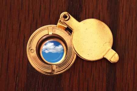 looking at viewer: Peephole to the better world. Close up of door viewer and cloudy sky Stock Photo
