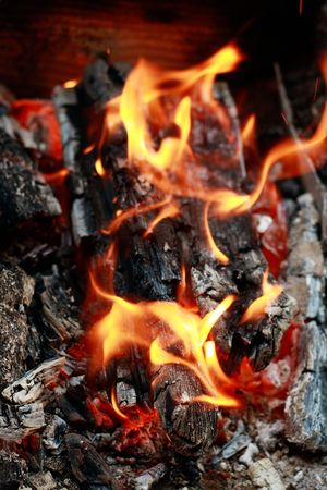 Home fireplace. Red fire and black ash abstract background photo