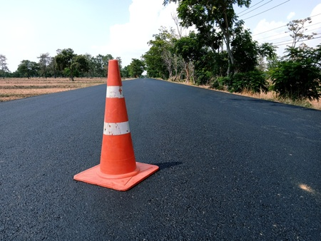 The road is currently under construction and has not yet hit the traffic line and there is a red rubber cone on the road as the front.