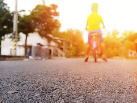 A boy standing with a bicycle in the middle of the road By waiting for his father to return home (picture blurred) Banque d'images - 132015142